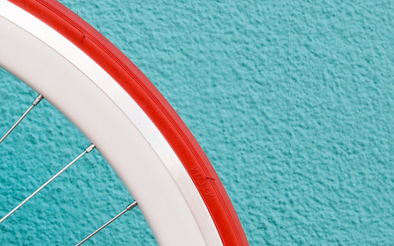 red, white-rimmed bicycle tire against a blue, cement wall
