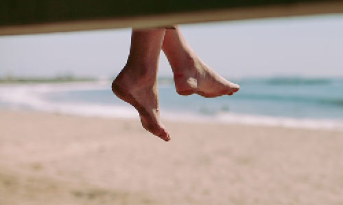 feet dangling off a pier over the sand as the waves break along the shore